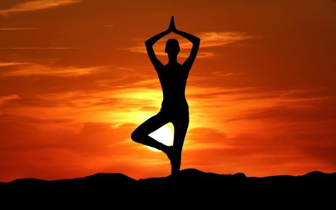 Sombra de mujer haciendo yoga en puesta de sol